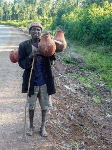 Man carrying jugs in Sidamo area coffee plantation,South Ethiopia
